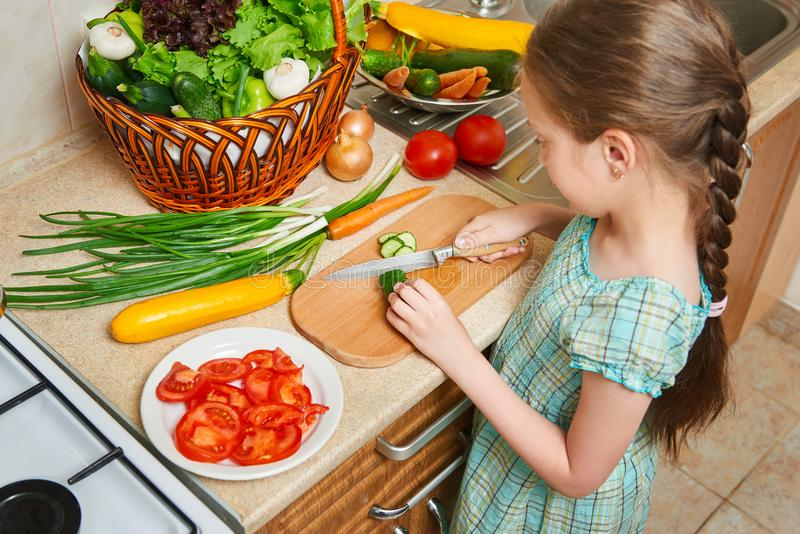 Child girl cooking in home kitchen. Basket of vegetables and fresh fruits in kitchen interior. Healthy food concept stock photo