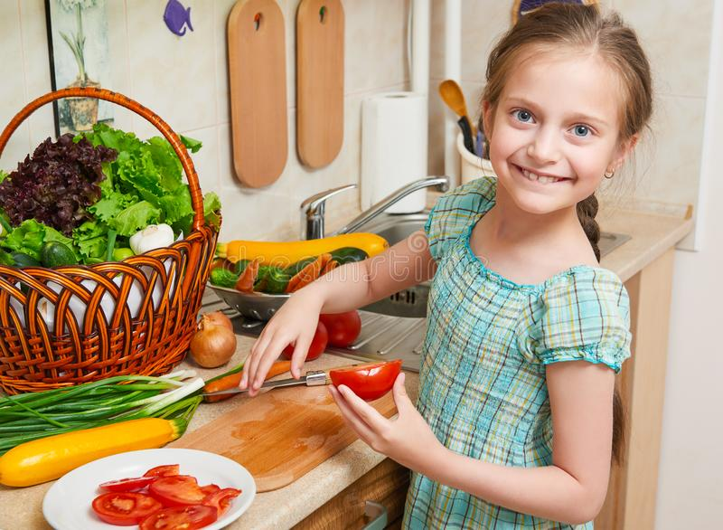 Child girl cooking in home kitchen, chopping tomatoes. Basket of vegetables and fresh fruits in kitchen interior. Healthy food con stock image