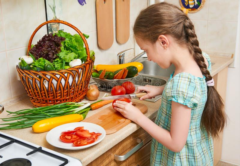 Child girl cooking in home kitchen, chopping tomatoes. Basket of vegetables and fresh fruits in kitchen interior. Healthy food con stock images