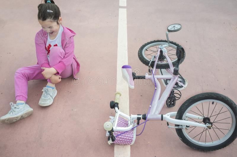 Child girl crying after bike accident. Pink female bike on floor with training wheels royalty free stock image