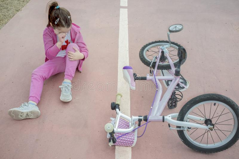 Child girl crying after bike accident. Pink female bike on floor with training wheels stock photo