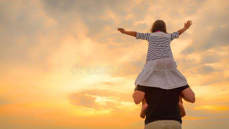 Child girl on dad`s shoulders on the background of the setting sun on a beach stock photo