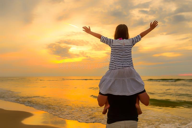 Child on dad`s shoulders on the background of the setting sun on a seaside beach royalty free stock photography