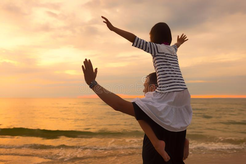 Child on dad`s shoulders on the background of the setting sun on a seaside beach royalty free stock image