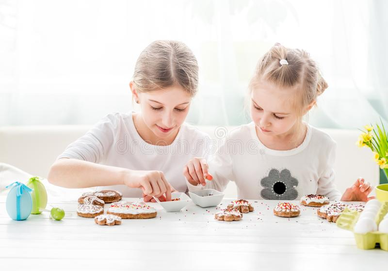 Child girl decorating Easter cookies stock photo