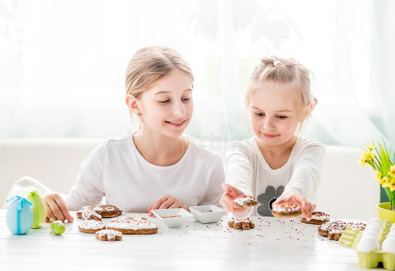 Child girl decorating Easter cookies stock images