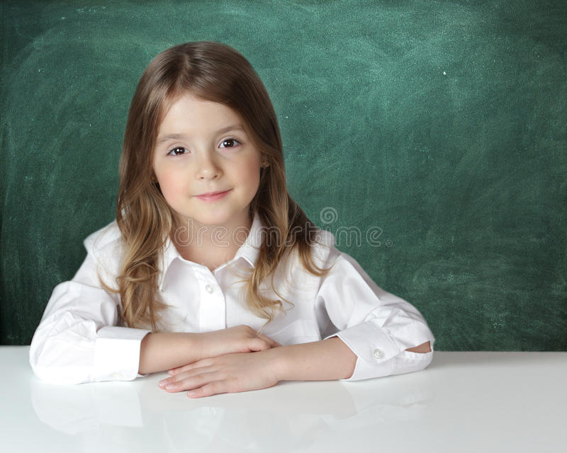 Child girl at desk chalk board background. stock image