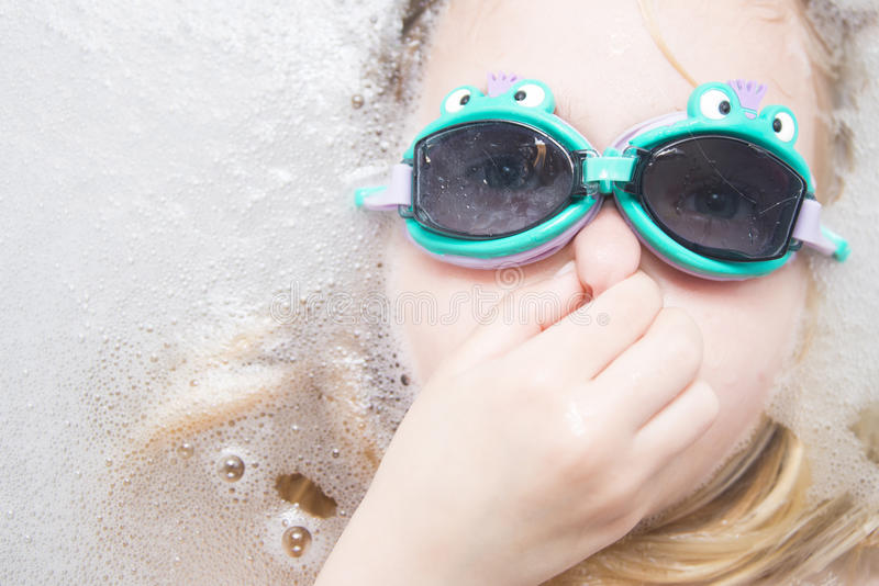 Child girl with diving goggles dive in the bathtub stock photo