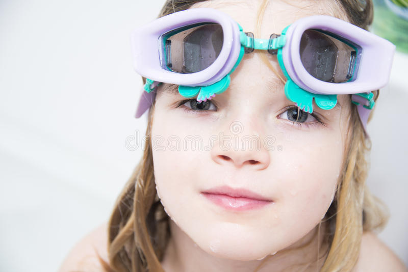 Child girl with diving goggles dive in the bathtub stock photography