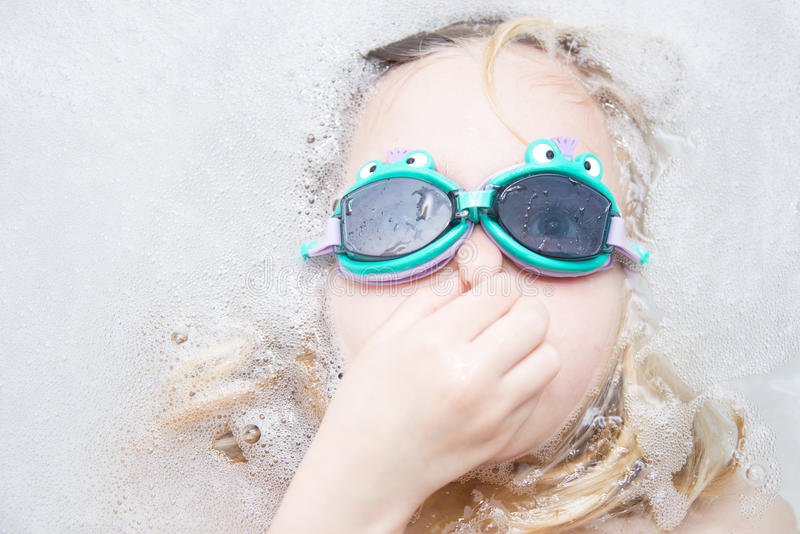 Child girl with diving goggles dive in the bathtub royalty free stock image