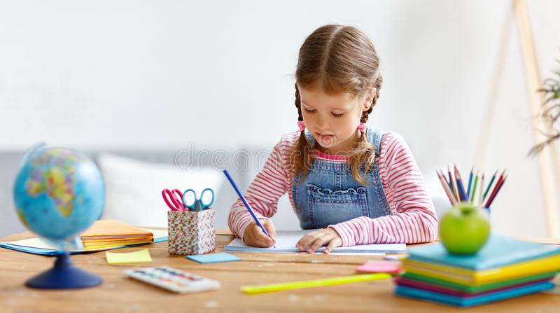 Child girl doing homework writing and reading at home. A child girl doing homework writing and reading at home stock images