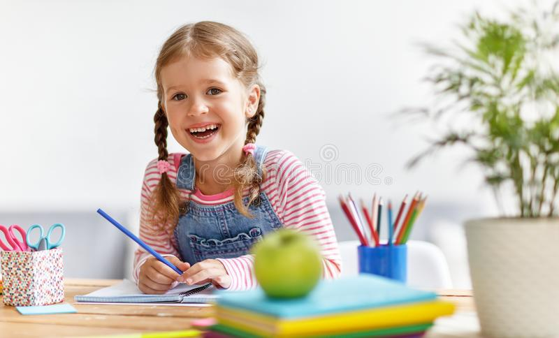 Child girl doing homework writing and reading at home. A child girl doing homework writing and reading at home stock photo