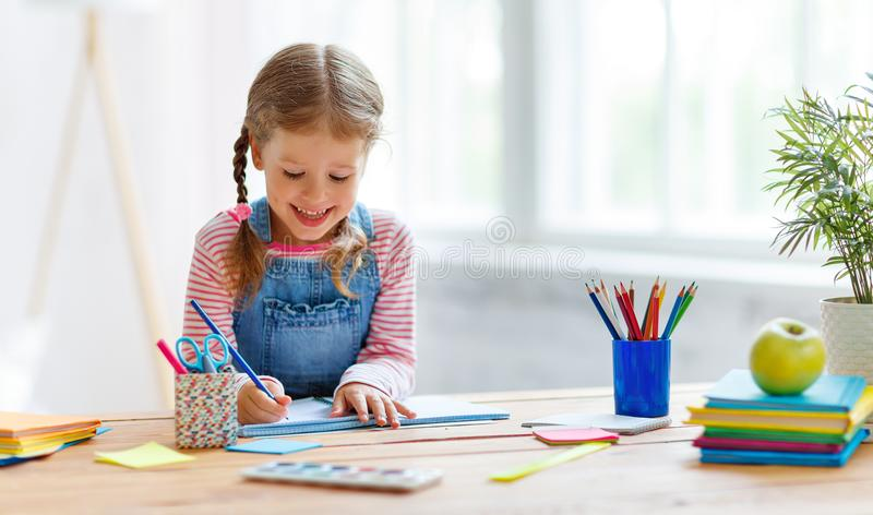 Child girl doing homework writing and reading at home. A child girl doing homework writing and reading at home royalty free stock photography