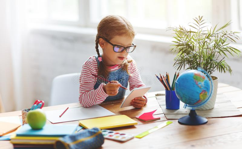 Child girl doing homework writing and reading at home. A child girl doing homework writing and reading at home royalty free stock images