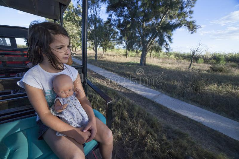 Child girl with doll at Mini-train of Barril Beach. Tavira, Portugal - October 14th, 2018: Child girl with doll at Mini-train of Barril Beach. This train stock photo