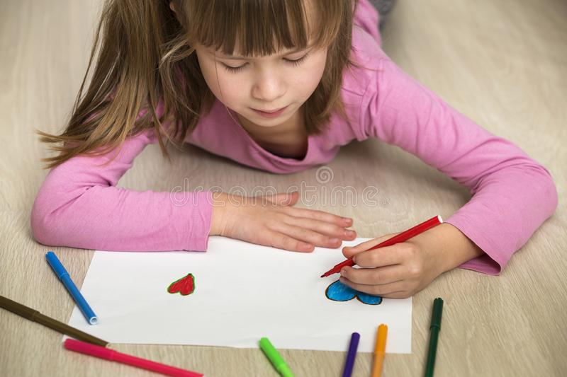Child girl drawing with colorful pencils crayons heart on white paper. Art education, creativity concept royalty free stock image