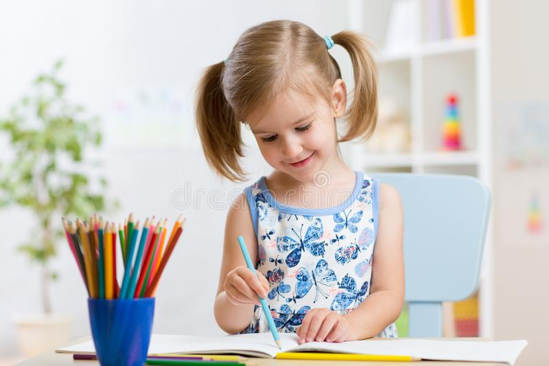 Child girl drawing with colorful pencils in nursery royalty free stock images