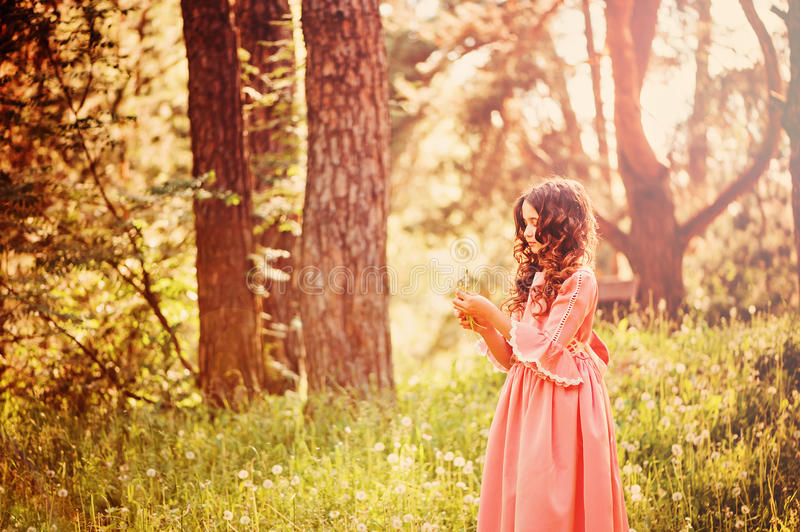 Child girl dressed as fairytale princess playing with blow ball in summer forest. Beautiful child girl dressed as fairytale princess playing with blow ball in royalty free stock photo