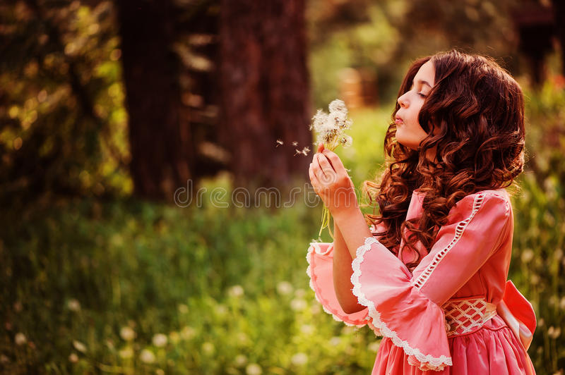 Child girl dressed as fairytale princess playing with blow ball in summer forest. Beautiful child girl dressed as fairytale princess playing with blow ball in stock photo