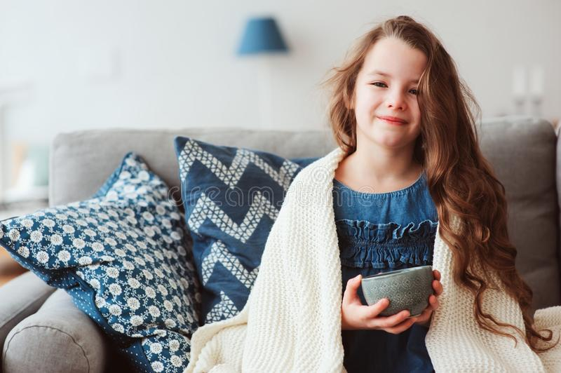 child girl drinking hot tea to recover from flu stock photos