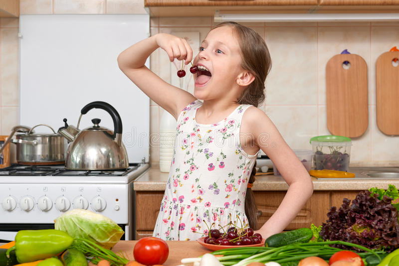 Child girl eat cherries, fruits and vegetables in home kitchen i royalty free stock images