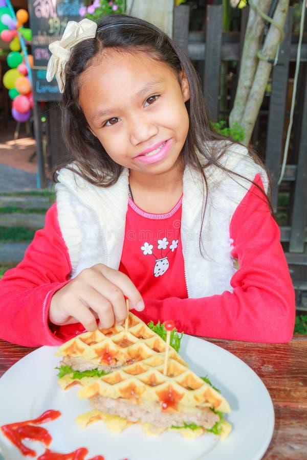 Child girl eat waffles pork royalty free stock photos