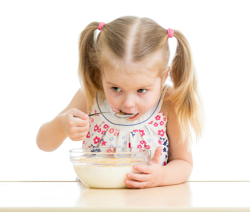 Child girl eating corn flakes with milk stock photography