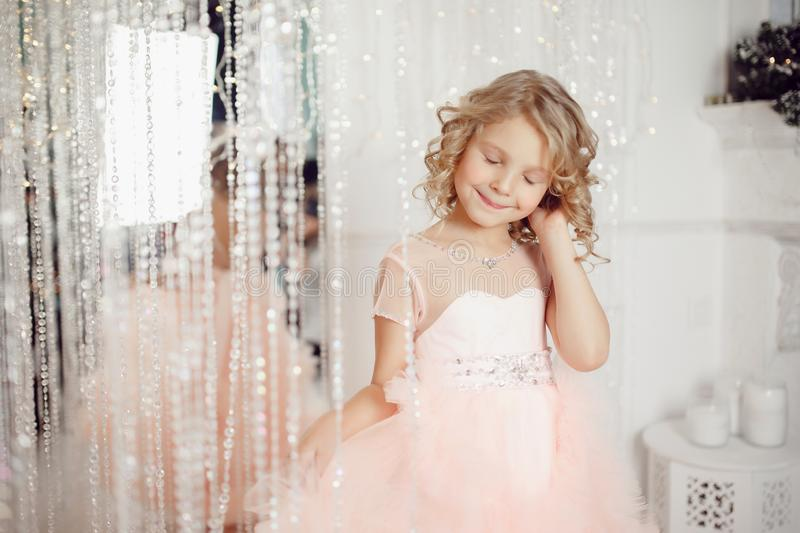 Child girl embarrassment in New Year interior, beautiful dress. royalty free stock photo