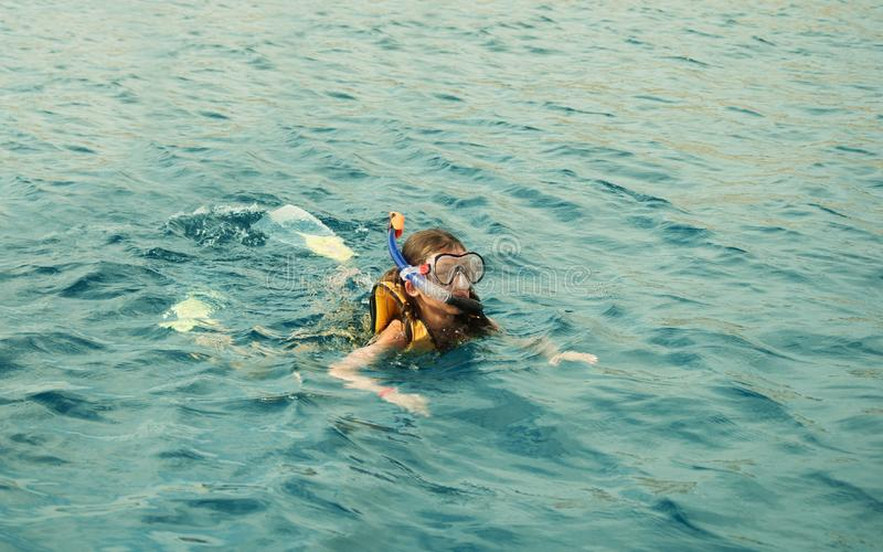 Child, a girl floats in the sea royalty free stock image