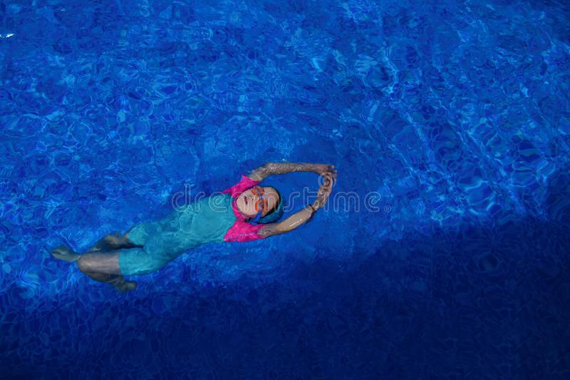 Child girl in goggles, swimsuit and cap is training swimming in pool. royalty free stock images