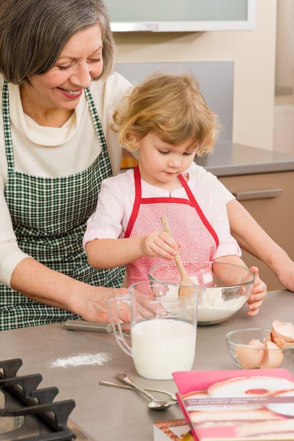 Child girl and grandmother baking cake. Stir flour royalty free stock photos