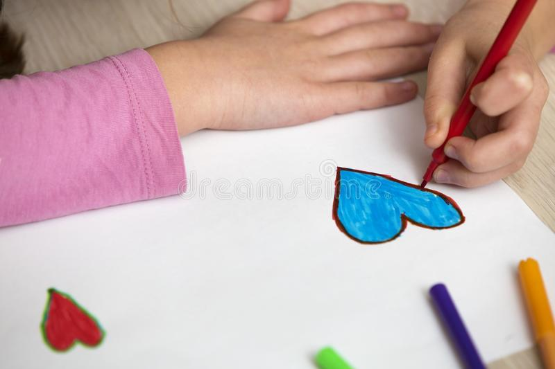 Child girl hands drawing with colorful pencils crayons heart on white paper. Art education, creativity concept.  royalty free stock photos