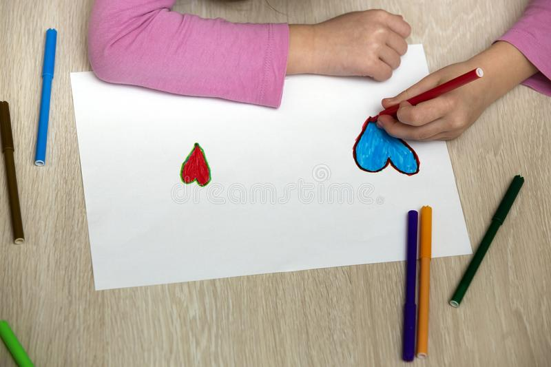 Child girl hands drawing with colorful pencils crayons heart on white paper. Art education, creativity concept.  royalty free stock photography
