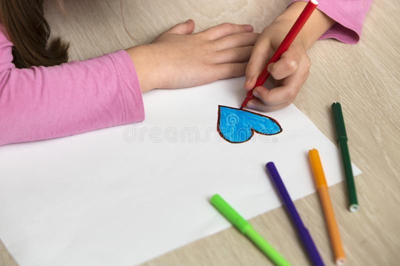 Child girl hands drawing with colorful pencils crayons heart on white paper. Art education, creativity concept.  stock photos