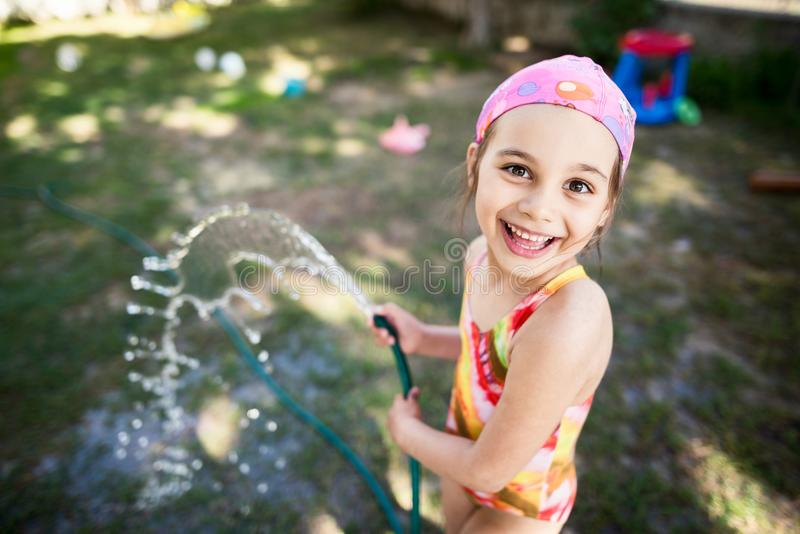 Child Girl Having Fun in the Garden with Water Outdoors royalty free stock photos