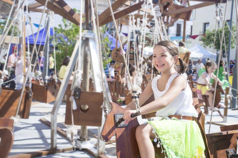 Child girl having fun at Human powered carousel. Motion blurred shot royalty free stock image