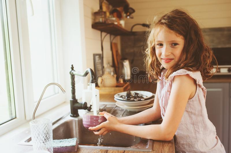 Child girl helps mother at home and wash dishes in kitchen. Casual lifestyle in real interior stock photo