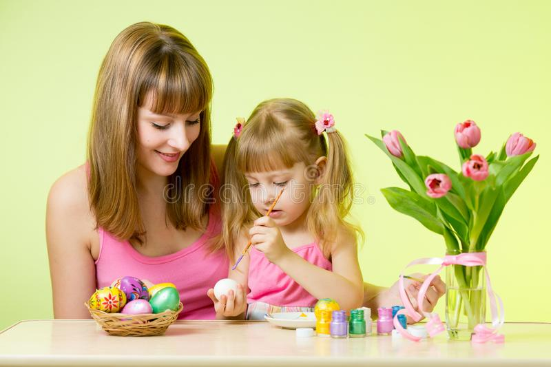 Child girl with her mom coloring Easter eggs at home royalty free stock image