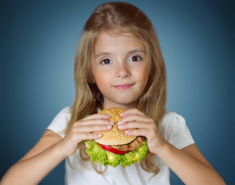 Child girl holding hamburger. Kid with fastfood sandwich. royalty free stock photos