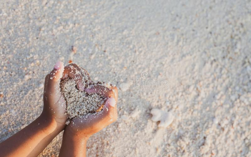 Child girl holding sand make heart shape in hands and playing on the beach stock photos