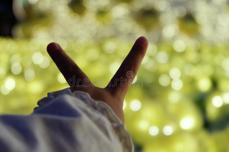 Child girl holding the two fingers forward. Ahead of her. on bokeh background , A symbol of peace and victory or fighting royalty free stock photography