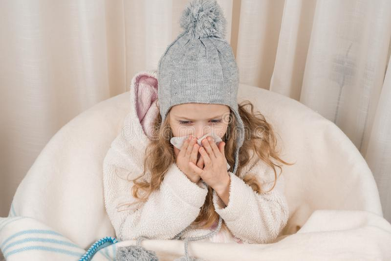 Child girl at home in chair with warm knitted hat woolen blanket sneezes in handkerchief. Season autumn winter colds royalty free stock photography