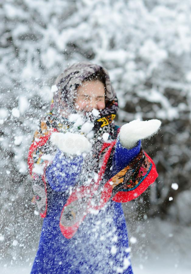 Free Child Girl In Shawl And Bright Blue Coat Stands In Winter Forest Or Park And Throws Snow With Hands. Stock Image - 166231121