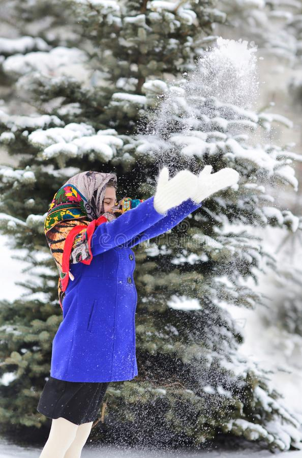 Free Child Girl In Shawl And Bright Blue Coat Stands In Winter Forest Or Park And Throws Snow With Hands Throws Snow Into The Air . Royalty Free Stock Photo - 166230655