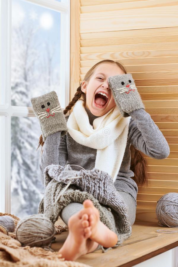 Free Child Girl Is Sitting On A Window Sill And Playing With Handmade Mitten. Beautiful View Outside The Window - Sunny Day In Winter Stock Photo - 134325030