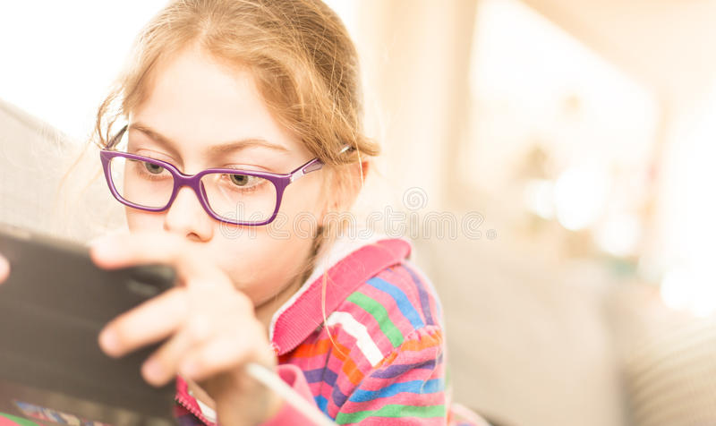 Child girl kid playing game on mobile phone at home. Eight years old, caucasian, blond child girl kid playing game on mobile phone smartphone. Childhood and stock photos