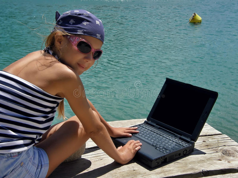 Child (girl) with laptop on sea royalty free stock photo