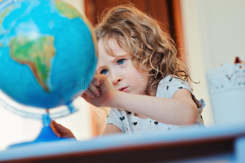 Child girl learning with globe at home stock photography