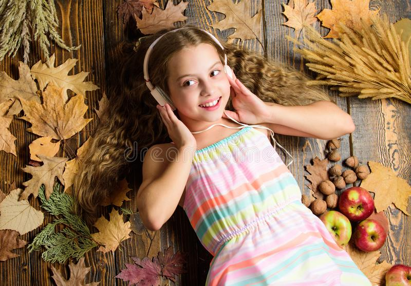 Child girl listen music headphones top view. Fall music playlist. Enjoy music and relax. Enjoy perfect sound. Girl lay royalty free stock image