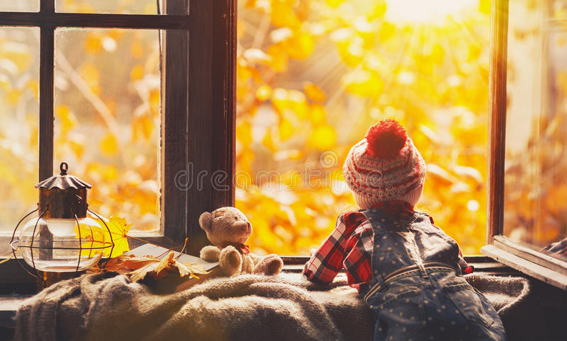 Child girl looking through open window at nature autumn. Child girl looking through the open window at the beautiful nature autumn gold royalty free stock photography